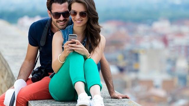 Casal usando celular em viagem